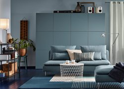 A medium sized living room furnished with a turquoise three-seat sofa and a footstool in the same color. Combined with a white storage table and a large storage combination in gray-turquoise.